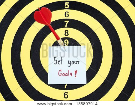 Handwriting Set Your Goals on notepaper with dart arrow and dart board. (Business concept)