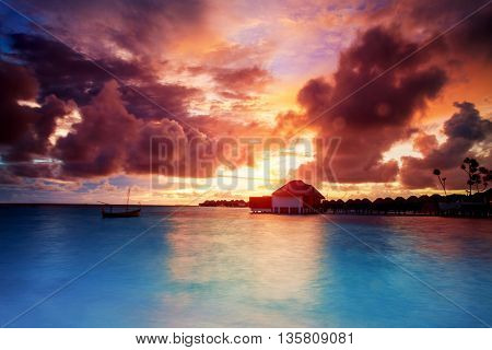 Sunset over Maldives islands, beautiful beach landscape, stunning evening seascape in orange sunset light, summer exotic holidays, travel and tourism concept
