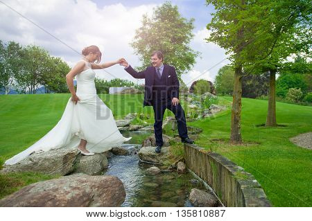 groom helps his wife walking up the river
