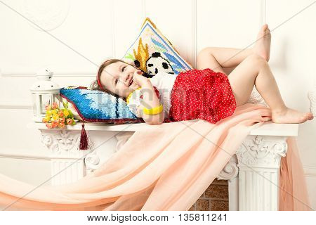 The child lying on the mantelpiece in white interior