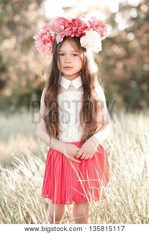 Cute baby girl 3-4 year old wearing peony wreath outdoors. Looking at camera. Childhood.
