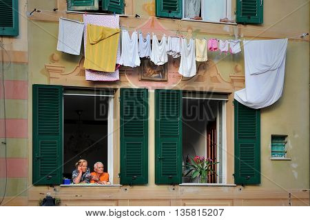 Camogli, Ligure, Italy - 19 September 2015: older couple in love look in the window    in Camogli, photo captured in an urban environment Camogli, Ligure, Italy. Illustrates the social life of the city, relationship of  people, loyalty and feelings love o