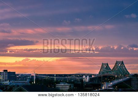 Montreal Jacques Cartier bridge over Saint Laurence river at sunset