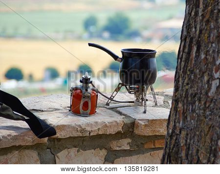 Making fresh hot coffee on a camping gas burner stove while hiking outdoors in nature