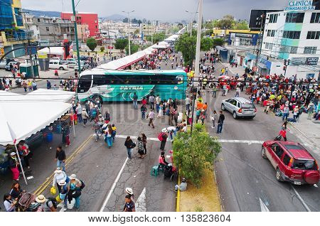 QUITO, ECUADOR - JULY 7, 2015: Cars an buses trying to pass in the middle of a crowded street, people walking to arrive to pope Fransisco mass.