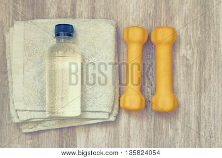 Fitness background with bottle of water, dumbbells and towel. View from above.