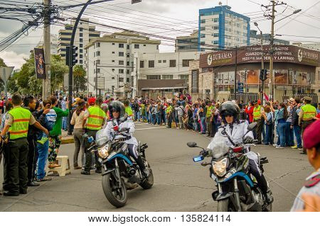 QUITO, ECUADOR - JULY 7, 2015: People waitting on the streets of the city, pope Francisco in his popemobile. Police making guards.