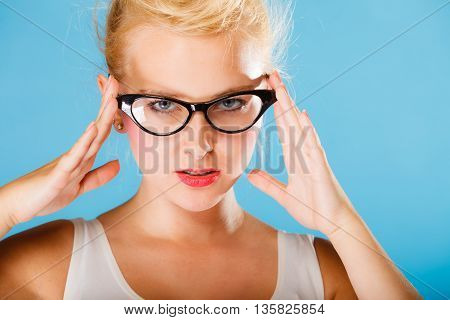 Optometrist oculist and ophthalmologist concept. Young blonde woman with eyeglasses on blue background in studio.
