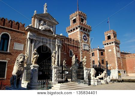 Venice, Italy - June 10, 2006:  Statues of lions and people flank the main facade of the Arsenal with its crenelated twin towers and lion of Venice doorway tympanum