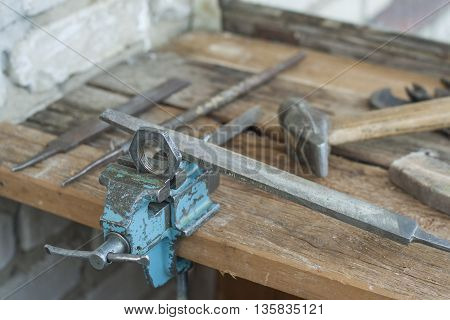 Nut for processing a file clamped in a vice on a wooden table. The old shop on the balcony of the old house.