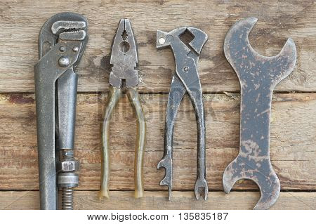 Bench set of tools on a wooden background with a wrench. The old shop.