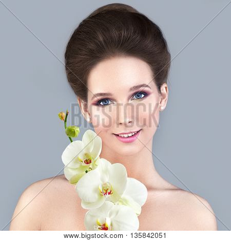Spa Skin Care Concept. Healthy Woman with Clear Skin and White Orchid Flower