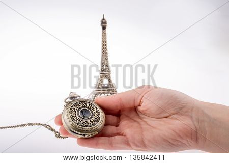 Hand holding a pocket watch befere Eifel Tower
