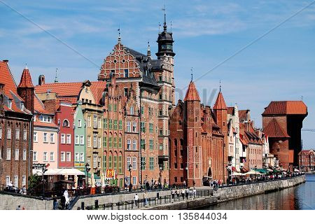 Gdansk Poland - May 30 2010: View over the Motlawa River to the splendid baroque 17-18th century houses lining Dlugie Pobrzeze (Old Quay) with the medieval Gdansk Crane