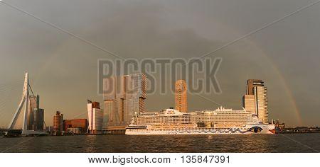 Cruiseship AIDA under a full rainbow docked in the harbor of Rotterdam near the Erasmus Bridge in June, 2016