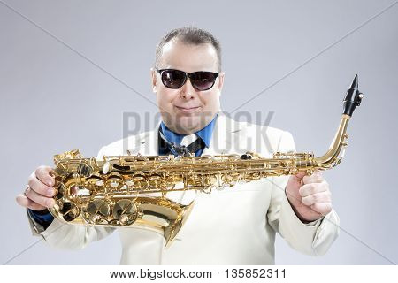 Smiling Happy Male Saxo Player in White Suit and Sunglasses Posing with Saxophone Against White Background.Horizontal Shot