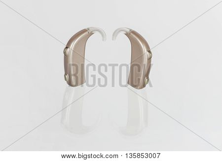 Two hearing aids on a reflecting glass surface