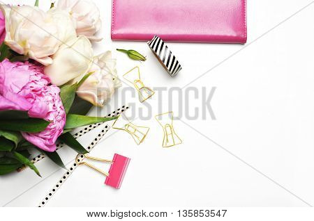 Flat lay. Peonies on the white background, view table. Up desk, stationery with notebook
