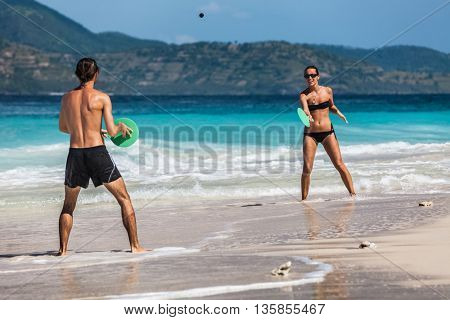 Young active couple playing tennis and having fun on the tropical beach