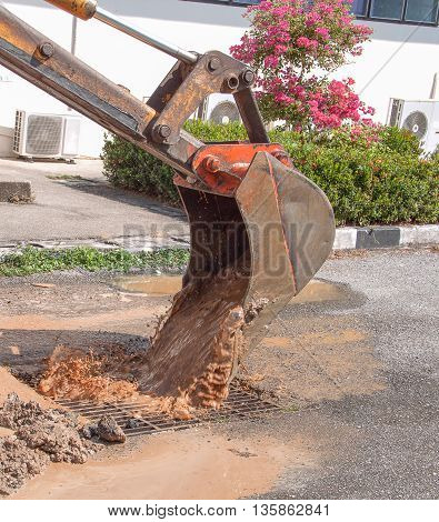 Excavator working on the Repair of pipe water and sewerage on the road, Worker using a small excavator to dig a hole to fix a water. (select focus on excavator and soft-focus water)