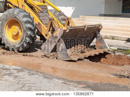 Yellow excavator on a construction and excavator scoop digging Repair of pipe water and sewerage on road worker fixing broken water main.(select focus front excavator)