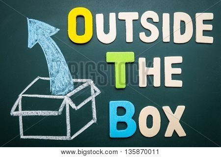 Outside the box wording with image drawing of box and arrow on blackboard - business concept of getting out of comfort zone