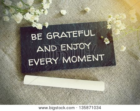 Blackboard for your text and flowers with words be grateful and enjoy every moment poster