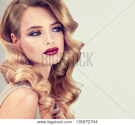 Blondel girl with long wavy hair .  Hairstyle Hollywood wave . Beautiful  model with curly hairstyle . Fashion makeup , wine lips and Smokey eyes .