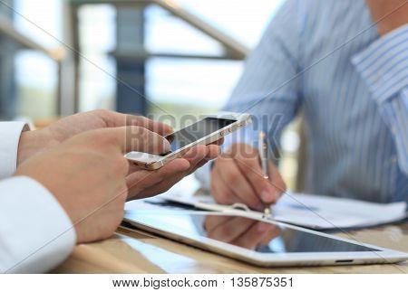 Smartphone handheld in closeup colleagues working in background.