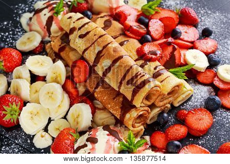 Sweet Rolled Pancakes with nutella, strawberry, blueberry, banana and ice cream.