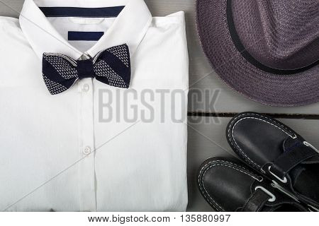 Men's outfit on wooden background. Kids fashion clothes. Grey fedora white shirt black bow tie and boat shoes for boy. Top view. Close up.