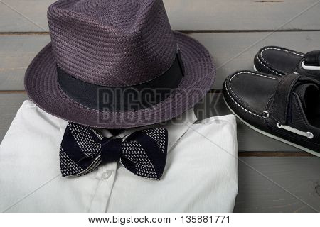 Men's outfit on wooden background. Kids fashion clothes. Grey fedora white shirt balck bow tie and boat shoes for boy. Close up.