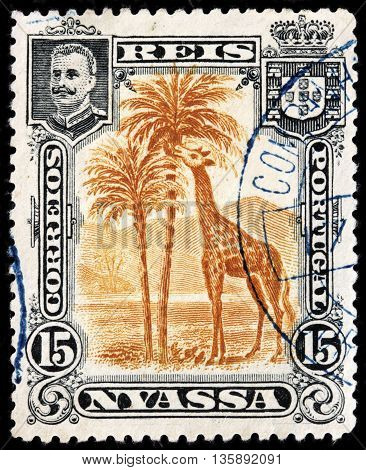 LUGA RUSSIA - JUNE 25 2016: A stamp printed by NYASSA shows image portrait of King Carlos I of Portugal against African landscape with giraffe. Niassa is a province of Mozambique circa 1901