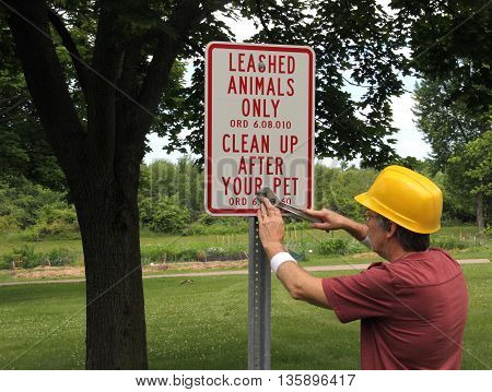 Park worker using a wrench to install an animal sign