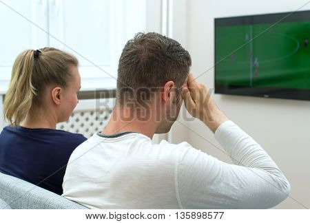 Sad couple watching football match on television at home.