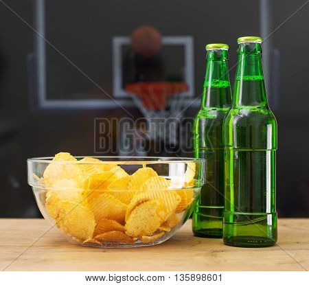Beer and chips in front of TV with basketball match.