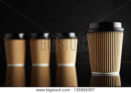 One focused coffee take away cardboard paper cup ahead others unfocused, all closed with black caps presented on black and mirrored. Retail mockup presentation