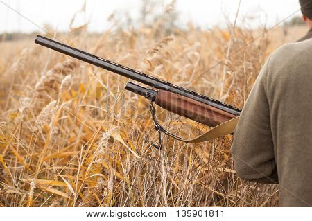 The hunter holds the gun. The man on hunting. Hunting for birds.