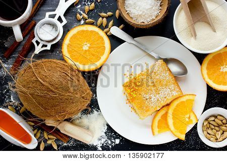 Semolina cake basbousa - traditional oriental dessert with sugar citrus syrup and coconut chips. Piece of cake and ingredients on black table top view food composition