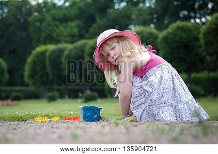 Little girl playing in the street. Baby in dress and hat sitting on his haunches. Bucket Toy rake and shovel. Summer heat green grass and trees