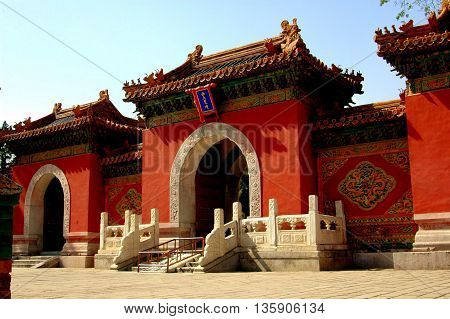 Beijing China - May 6 2005: Three gateways with rounded arches flanked by carved designs and tiled roofs with ceramic animal figures lead into the Heavenly King Hall Pavilion in Behei Park