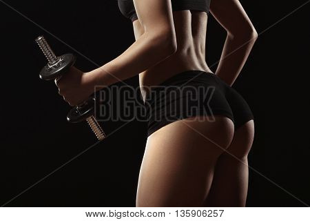 Sexy fitness ass close-up. Part of fitness body on a black background. Perfect female sports figure. Fitness woman posing in the studio. Fitness photo shoot in the studio. Fitness bikini