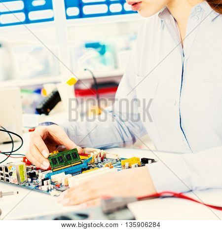 Woman  with a tester and a printed circuit board. Toned image