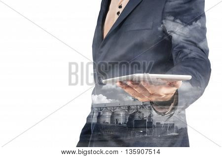 Double Exposure Of Businessman With Tablet Device And Silo Plant
