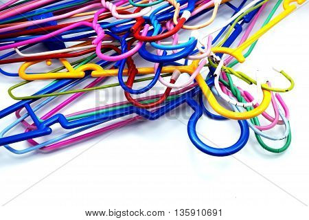 Heap of colorful clothes hangers on blue-white background. Space for texts.