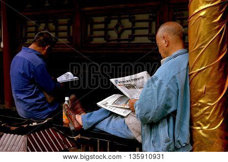 Chengdu China - September 20 2006: Two men reading Chinese newspapers sitting on a wooden gallery balustrade at the Da Ci Buddhist Temple