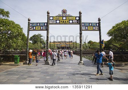 Hue, Vietnam - Jun 16, 2016: Visitors coming to see the Imperial Royal Palace of Nguyen dynasty at Ngo Mon gate. This gate is one of the forbidden city main gates.