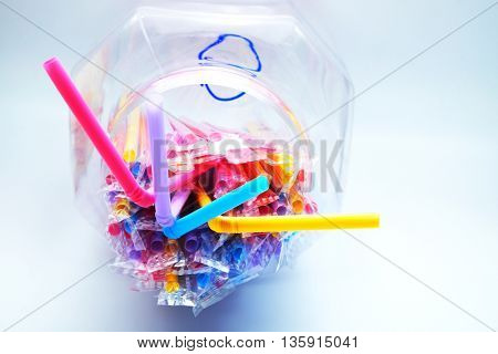 Colorful plastic drinking straws in plastic wraps with transparent bowl on blue-white background. Focus on extended straws. Space for texts.