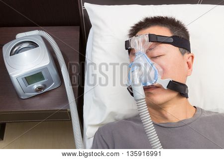 Asian man with sleep apnea using CPAP machine wearing headgear mask connecting to air tube selective focus on the man and headgear mask