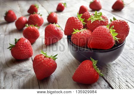 Strawberries fresh picked in a bowl on wood table antioxidant organic superfood concept for healthy eating and nutrition